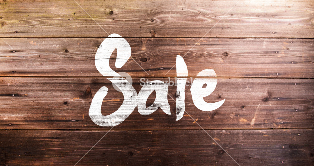 Chalk sale sign. Studio shot on wooden background.