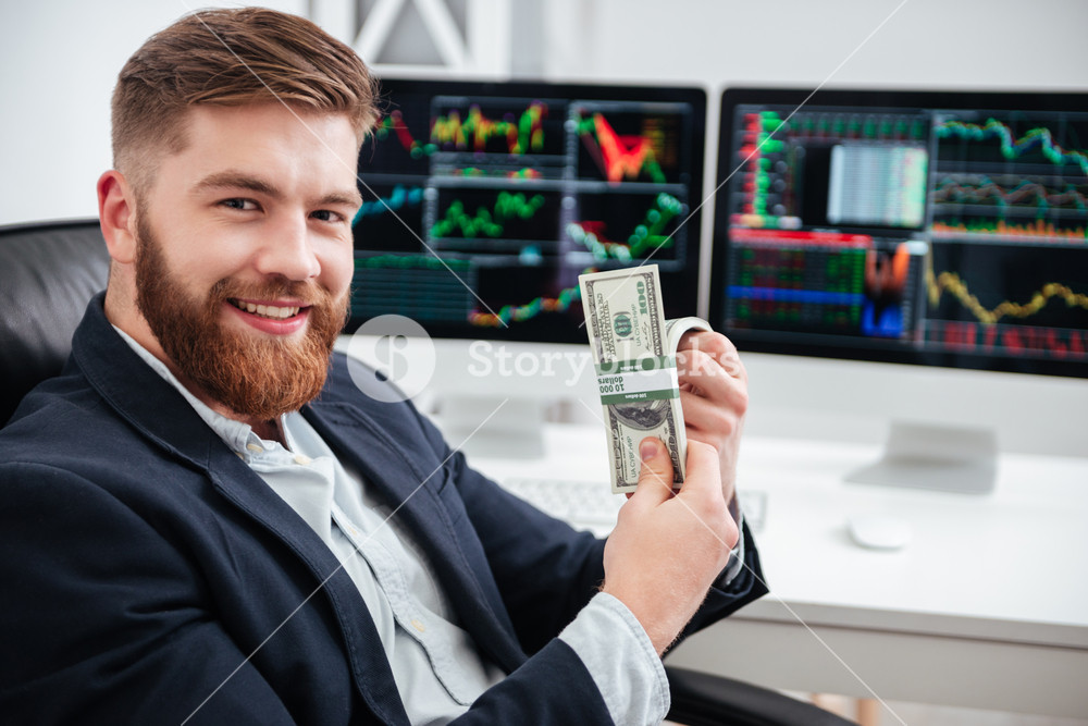 Cheerful bearded young businessman sitting and holding dollars in office
