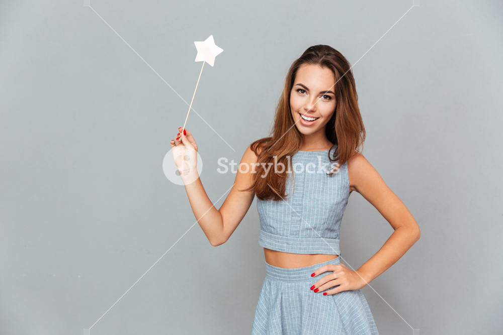 Cheerful beautiful young woman holding magic wand over grey background