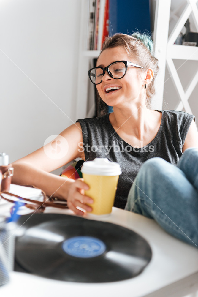 Cheerful relaxed young woman with cup of coffee sitting with legs on table and laughing