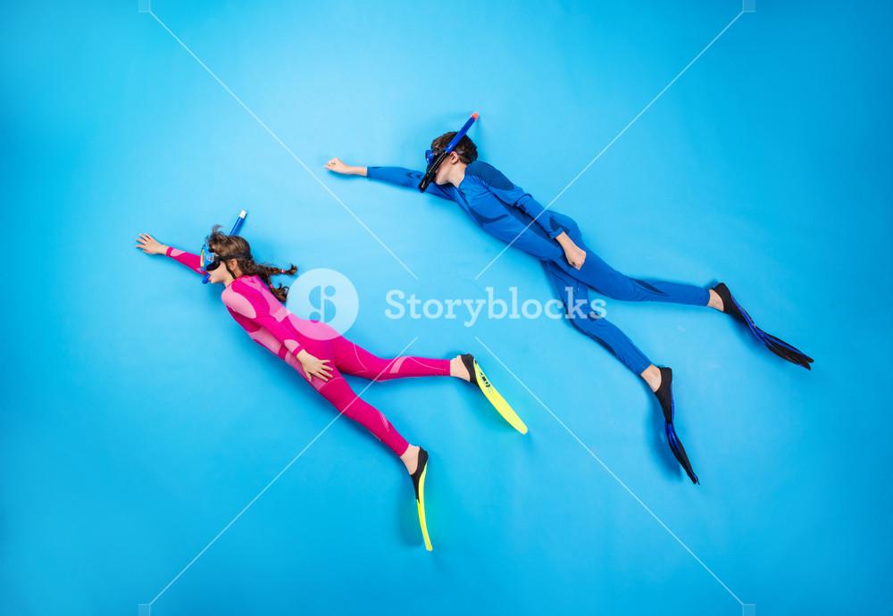Children scuba diving deep in the sea. Studio shot on a blue background.