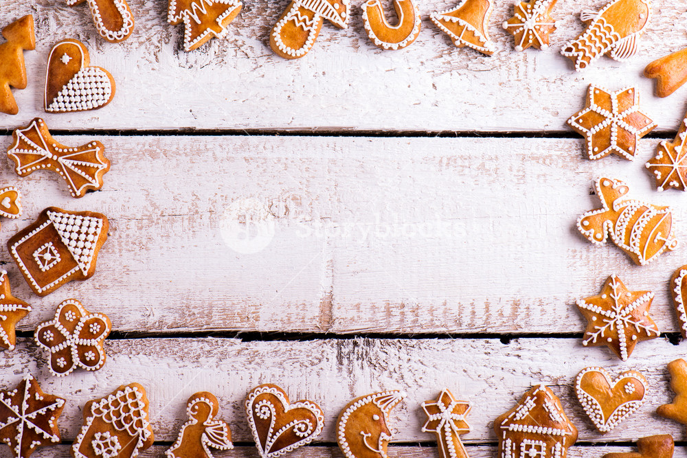 Christmas composition with gingerbreads. Studio shot on white wooden background.