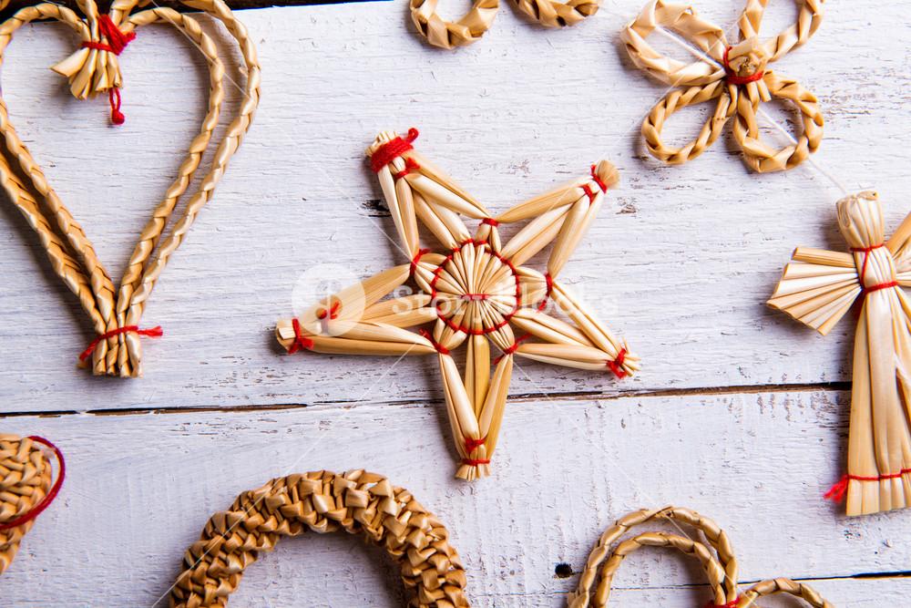 Christmas straw decoration. Studio shot on white wooden background.