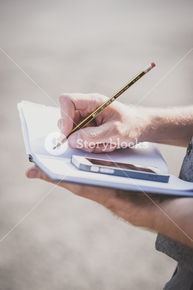 close up hands man writing on diary and smartphone outdoor