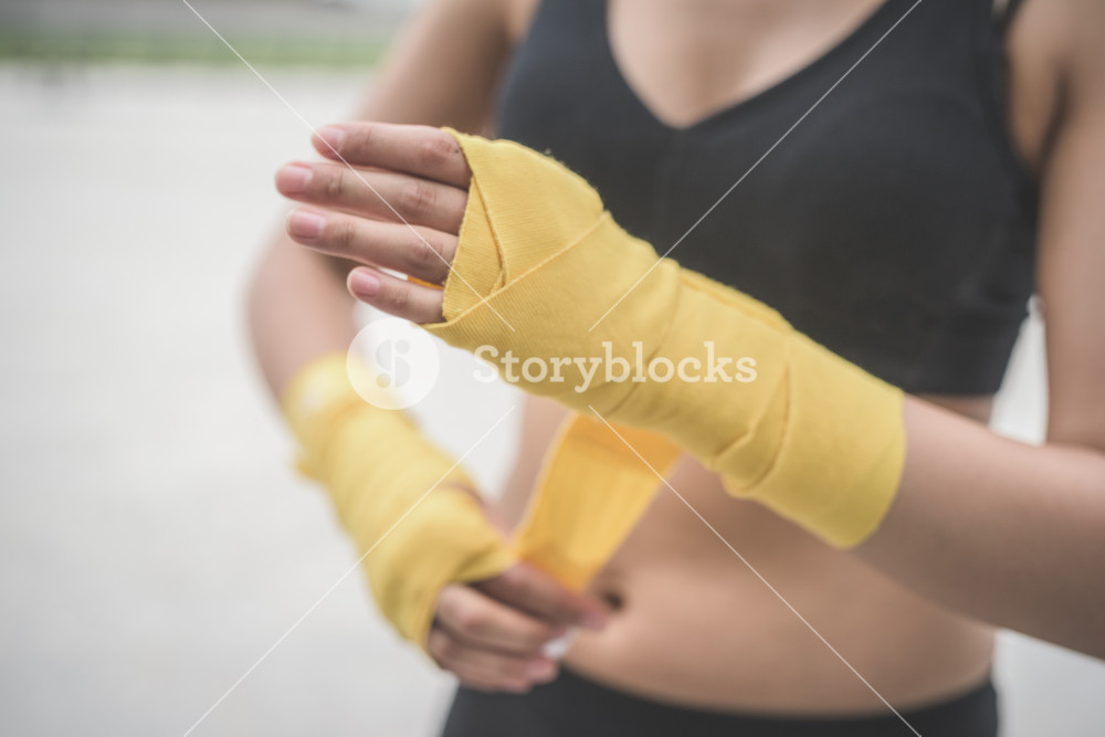 Close up of a young handsome caucasian brown hair woman wrapping her hands with a band, preparing herself for boxing training - sportive, healthy, fitness concept