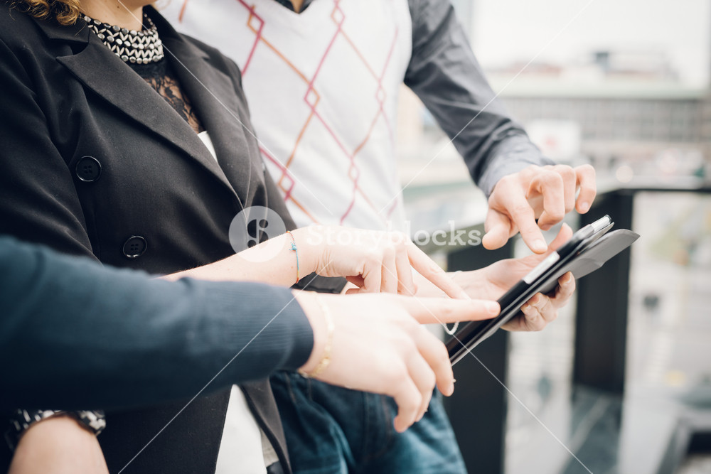 Close up of group of business people having a meeting outside in the city using tablet  - business, teamwork, multitasking, technology, meeting concepts - Focus on hands