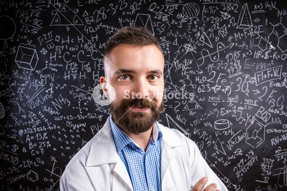Close up of hipster teacher in white coat standing against big blackboard with mathematical symbols and formulas. Studio shot on black background.