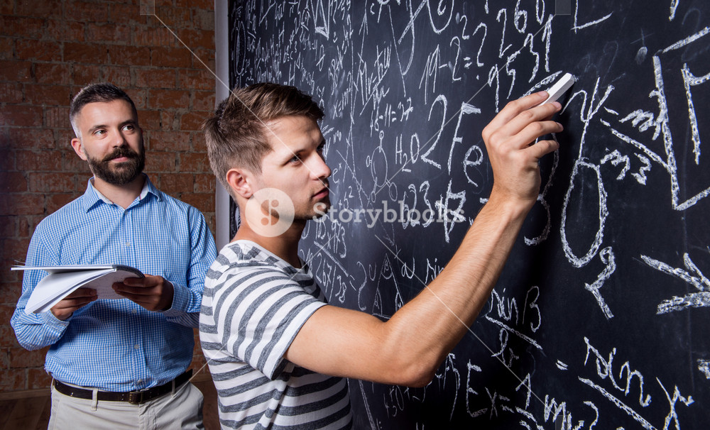 Close up of hipster teacher with his student writing on big blackboard with mathematical symbols and formulas. Studio shot on black background.