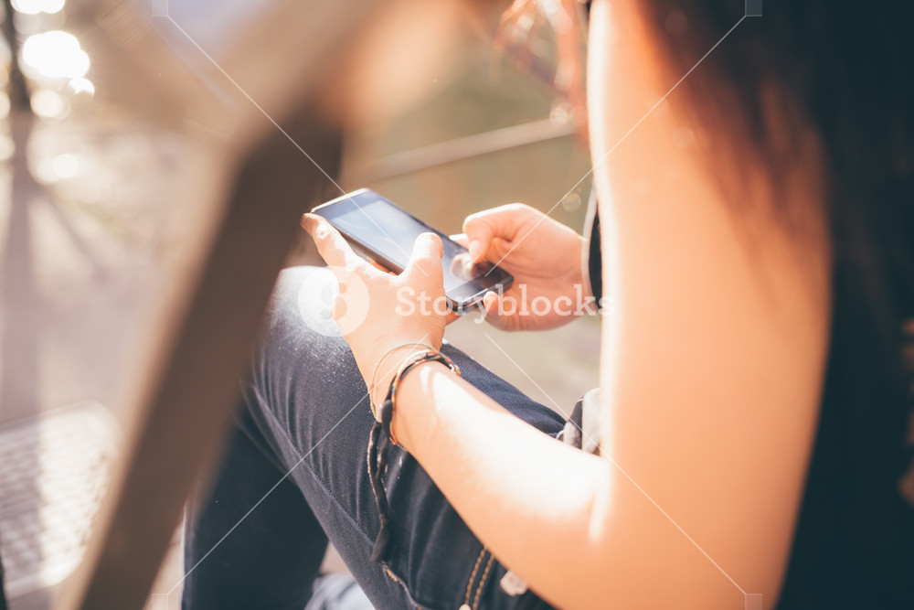 Close up of the hands of a woman reddish brown air using a smartphone seated on a staircase - technology, social network, communication concept - dressed with black shirt and blue jeans