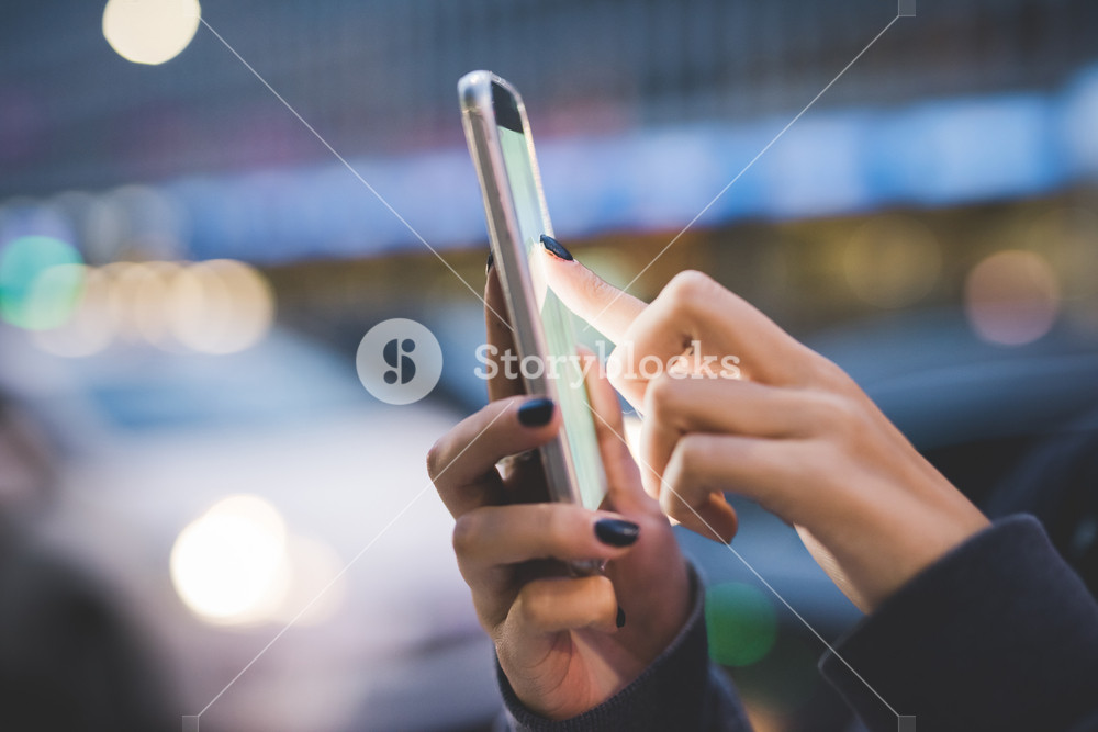 Close up on the hand of young woman using a smartphone, tapping the screen in city dusk - technology, communication, social network concept