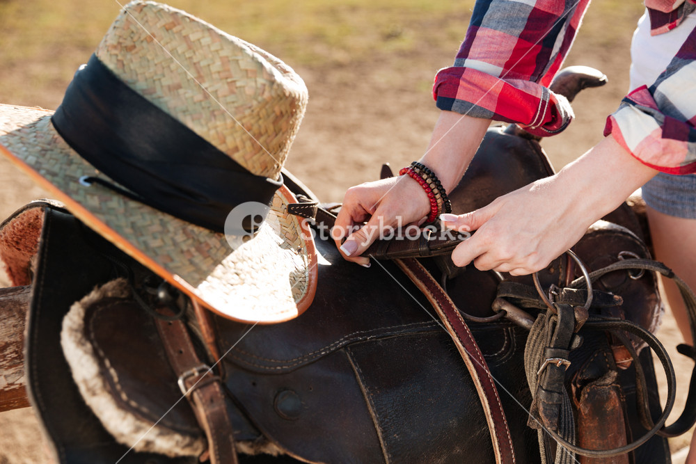 Closeup of saddle prepared for horse riding by young woman cowgirl