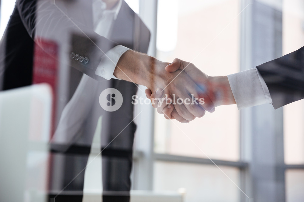Closeup of two businessmen standing and shaking hands in office