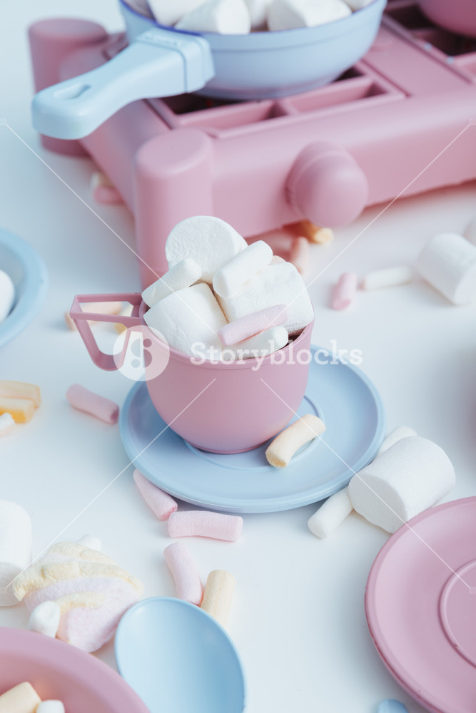 Colorful plastic dishes and marshmallows on white table