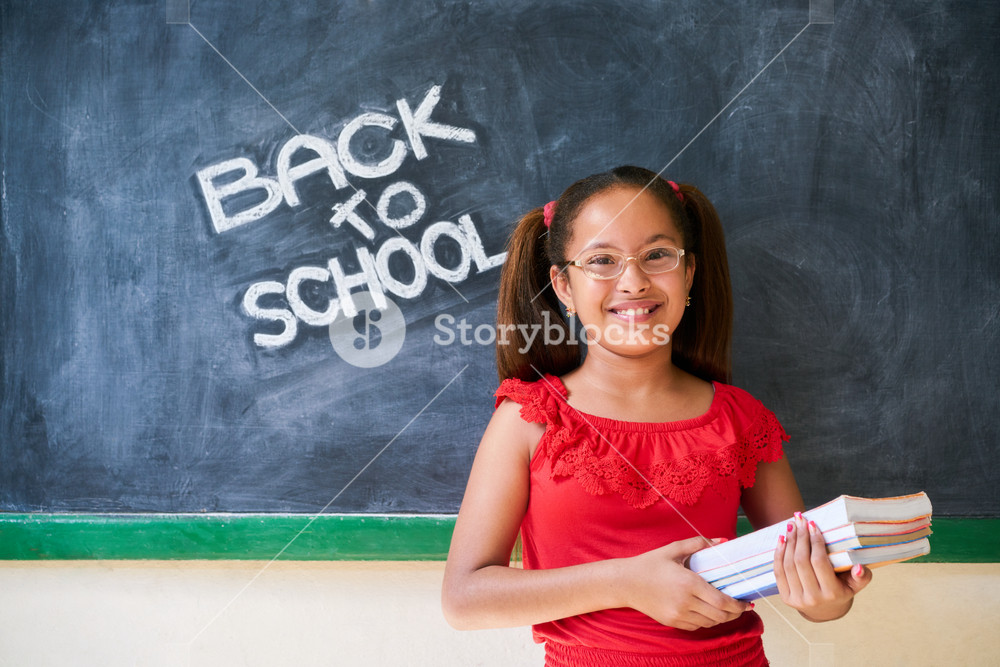 Concept on blackboard at school. Happy latina girl in class. Portrait of female child smiling, looking at camera, holding books. Back to school message