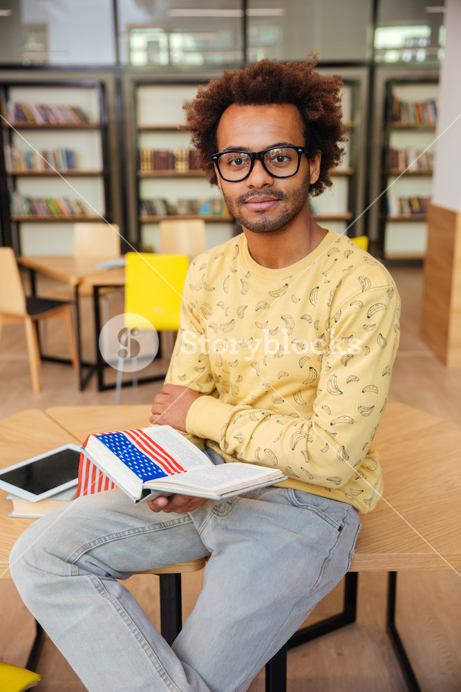 Confident african young man in glasses reading book in library