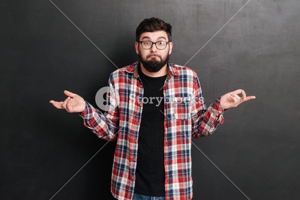 Confused bearded young man in glasses and plaid shirt standing and shrugging his shoulders over grey background