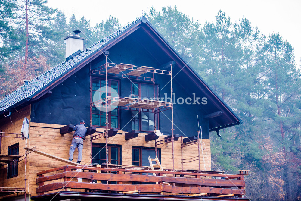 Construction worker standing on scaffold, thermally insulating house with glass wool and black foil, doing wooden facade.