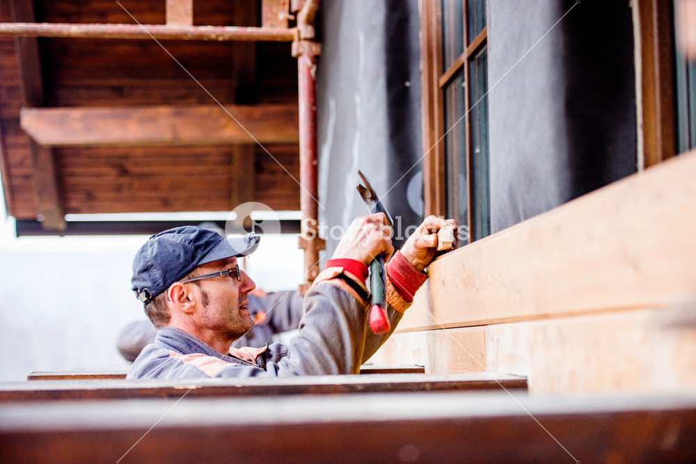 Construction worker thermally insulating house with glass wool and black foil, doing wooden facade.