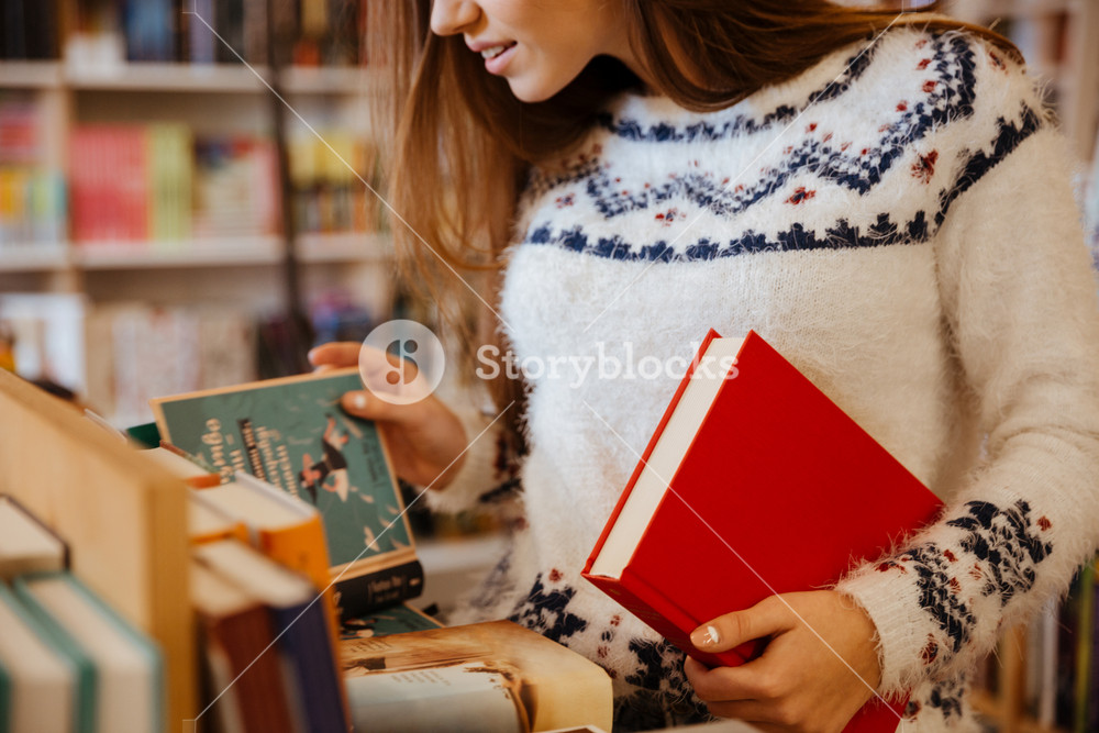 Cropped image of a young woman choosing books in library