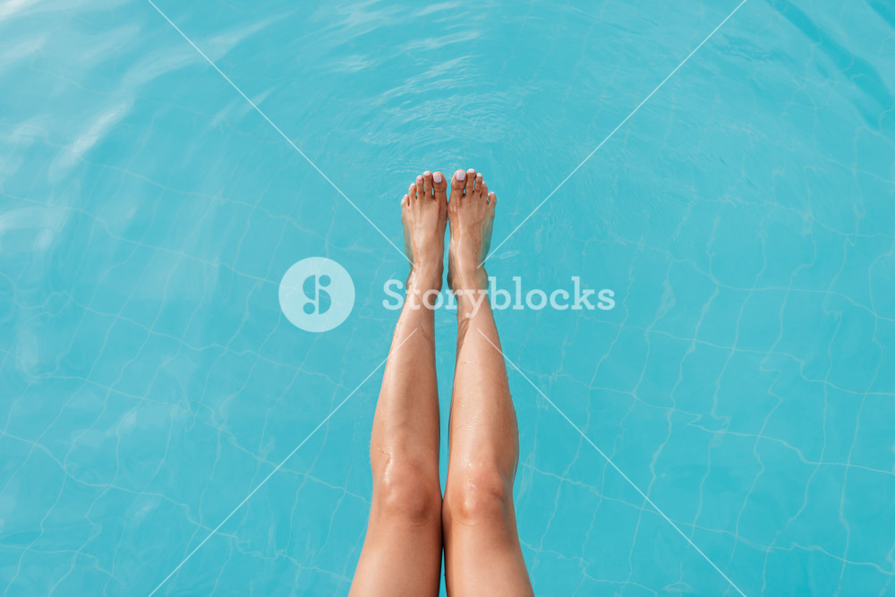 Cropped image of legs of woman which sitting near the pool and holding legs in water
