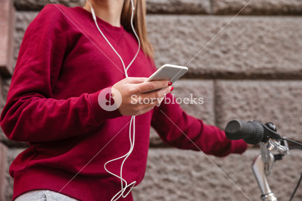 Cropped image of woman dressed in sweater walking with her bicycle in the city while standing near wall and listen to music by her phone.