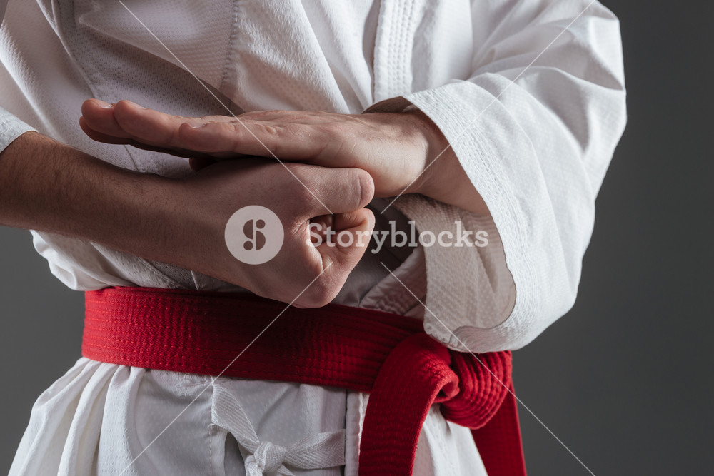Cropped photo of young sportsman dressed in kimono practice in karate and gesture with hand isolated over grey background.