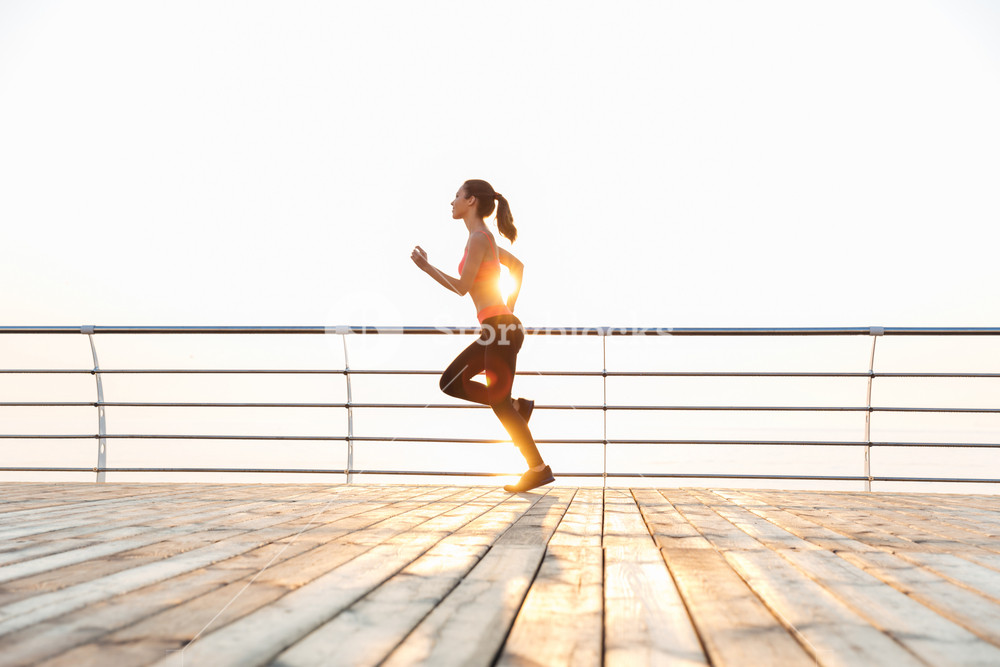 Cute young sportswoman running on pier in the morning
