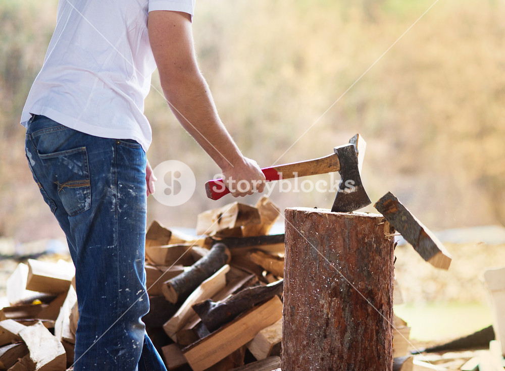 Detail of young man chopping wood in his backyard