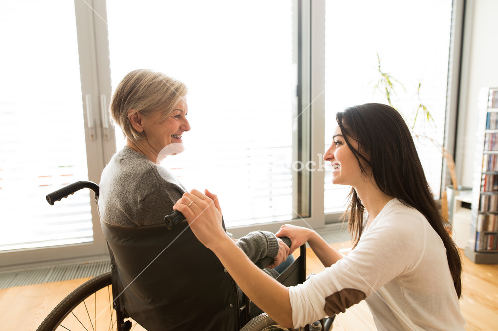Disabled senior woman in wheelchair at home in her living room, with her young daughter caring for her.