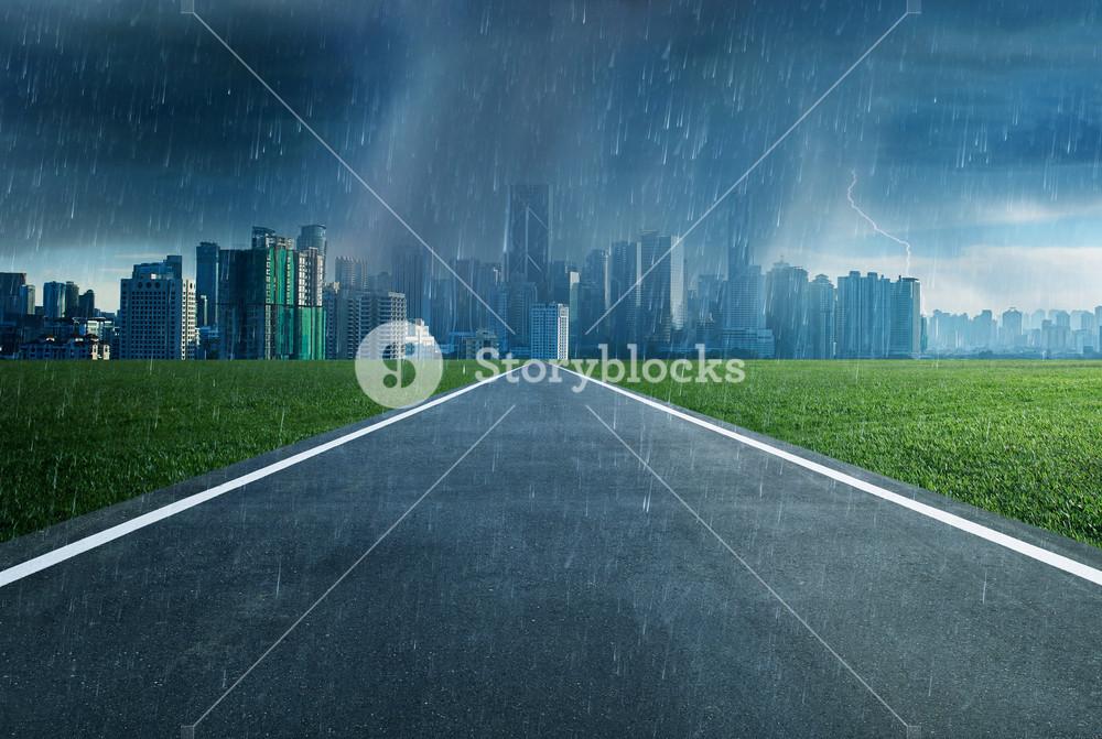 Empty asphalt road towards a city in storm