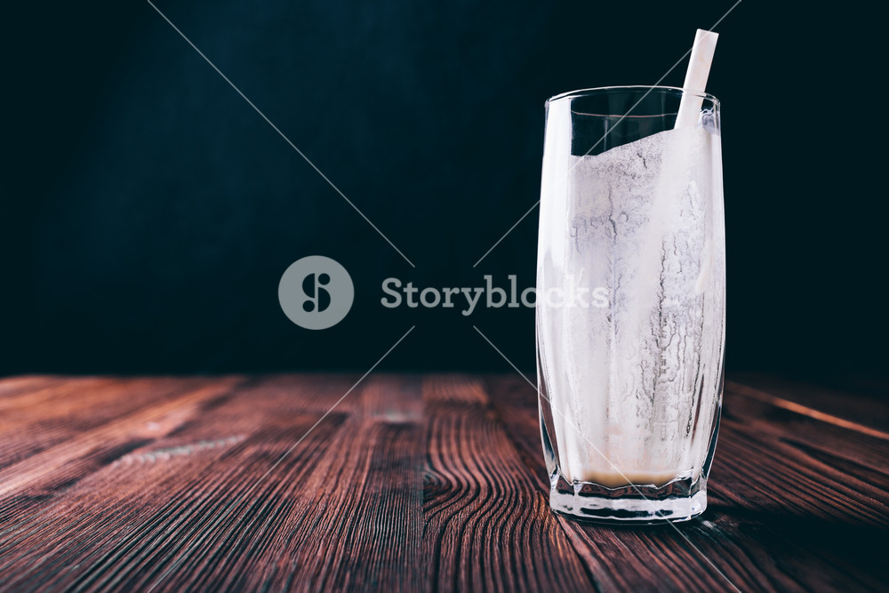 Empty glass from a milk smoothie on a table, dark background