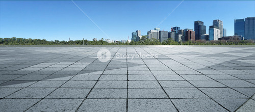 Empty marble floor with cityscape and skyline in clear blue sky