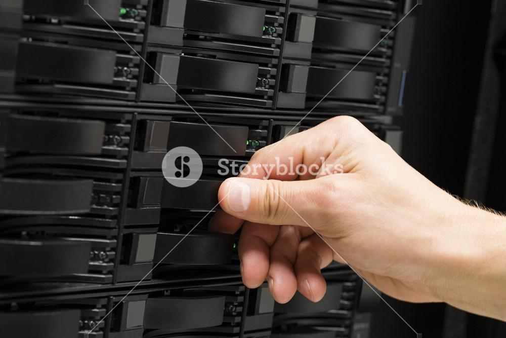 Engineer's Hand Replacing Hard Drive In SAN Storage