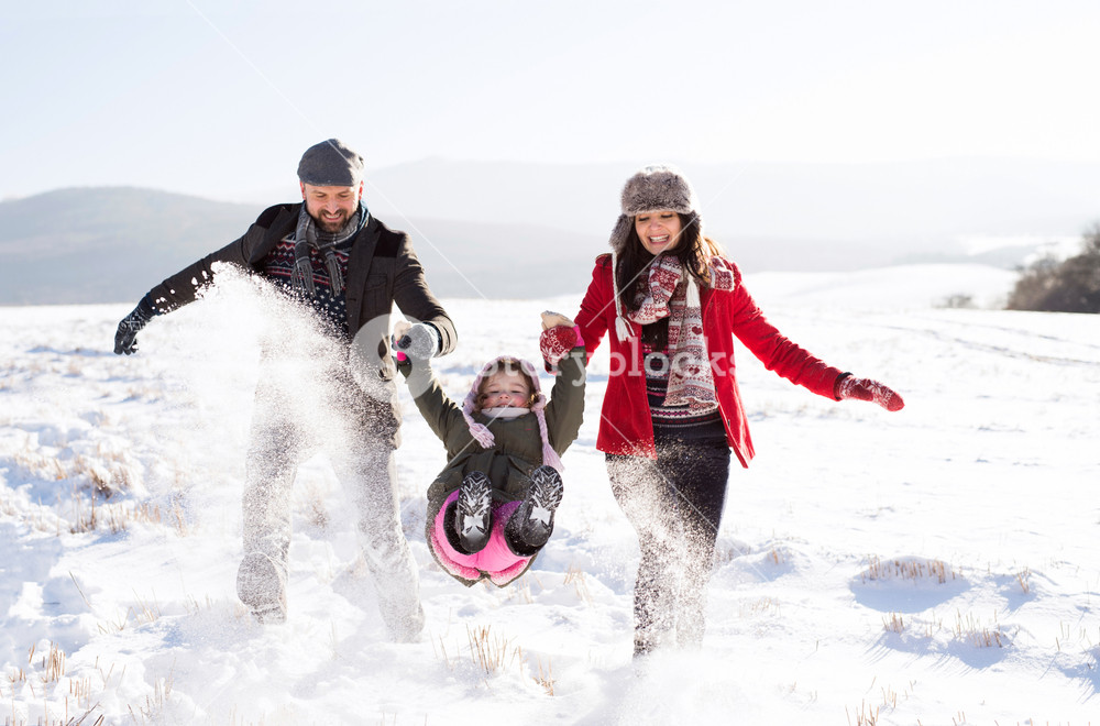 Father and mother having fun with their daughter, playing in the snow. Sunny white winter nature.