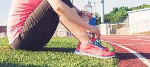 Female runner relaxing on the edge of a stadium track