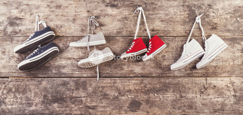 Four pairs of sports shoes hang on a nail on a wooden fence background
