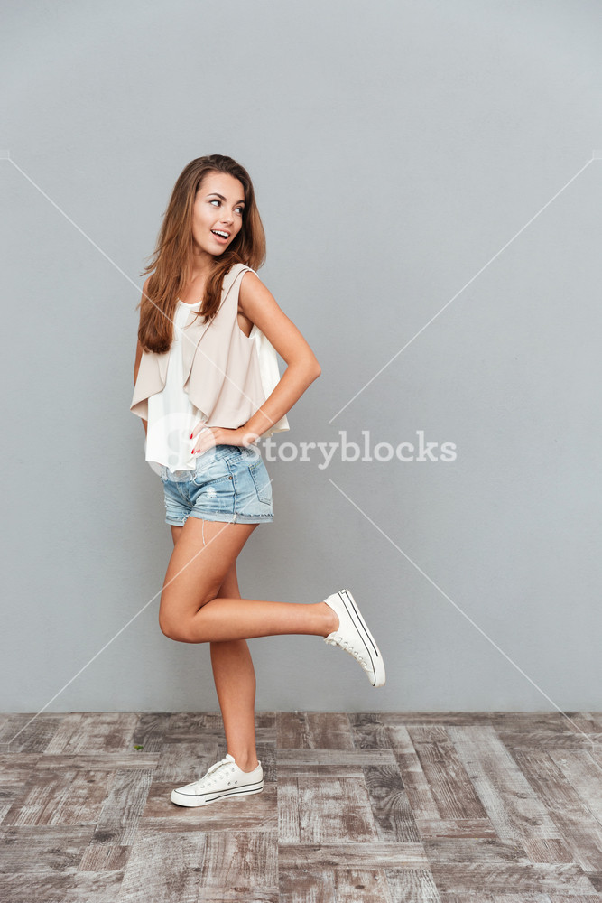 Full length portrait of a smiling cute woman posing isolated on a gray background