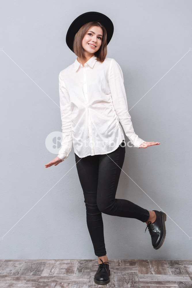 Full length portrait of a smiling young woman in hat standing and posing over gray background