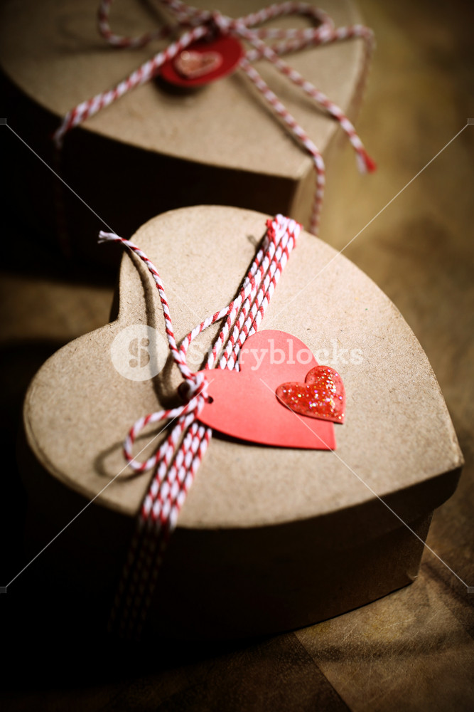 Gift boxes with handmade heart tags on wooden board