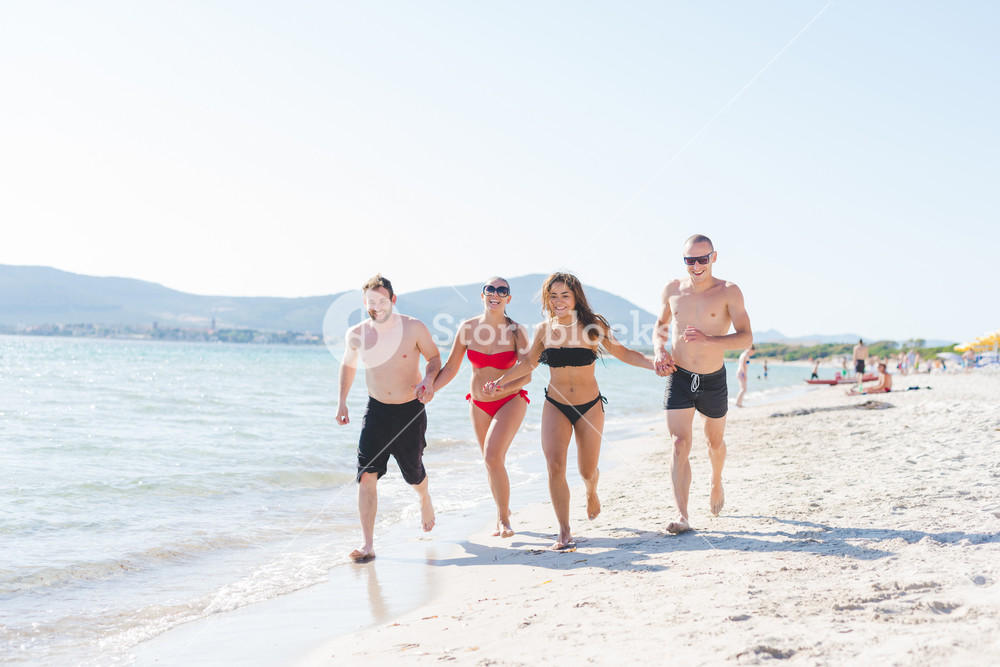 Group of friends millennials running holding hands on the seashore having fun - friendship, interaction, happiness concept