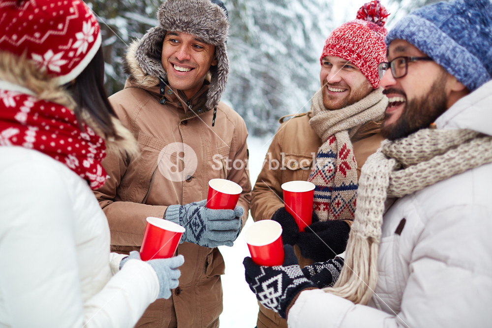 Group of friends with hot drinks spending leisure in winter environment