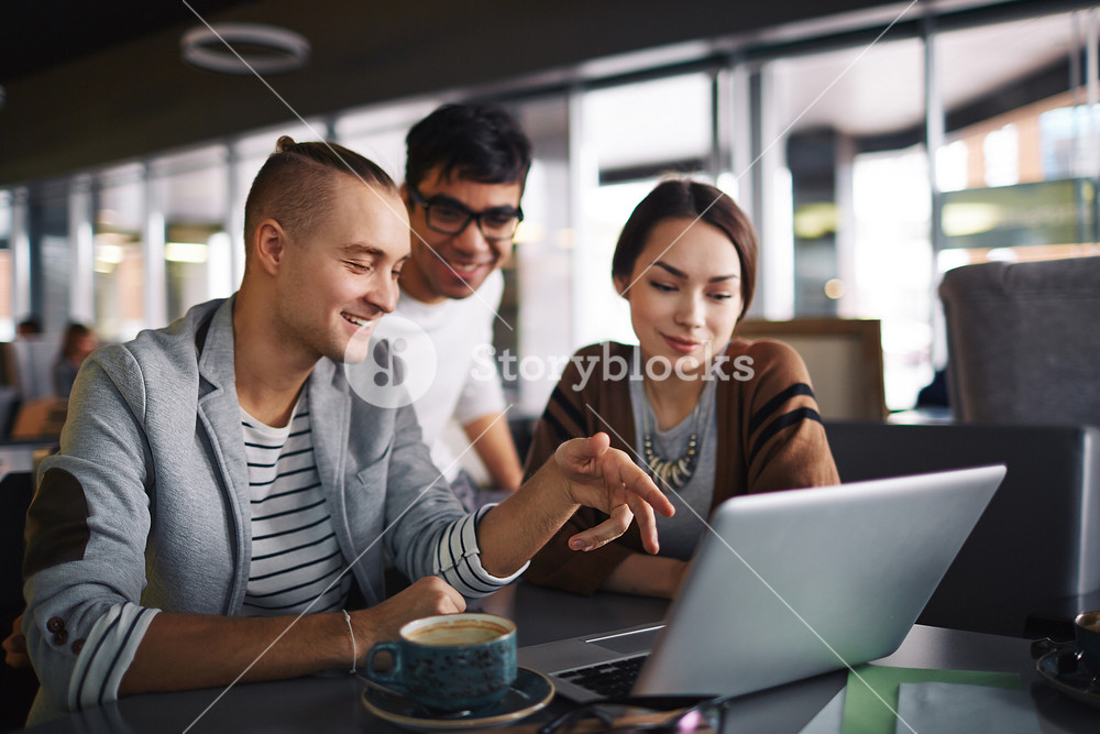 Group of friends with laptop spending leisure in cafe