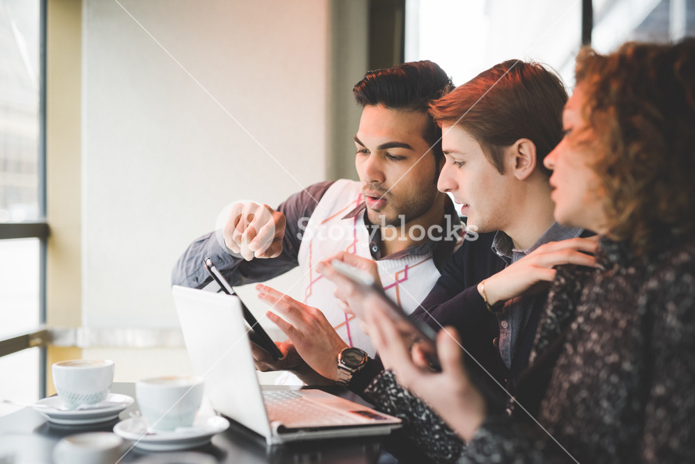 Group of multiracial business people working sitting in a bar having a coffee, connected with technological devices like smartphone, tablet and notebook - technology, working, business concept