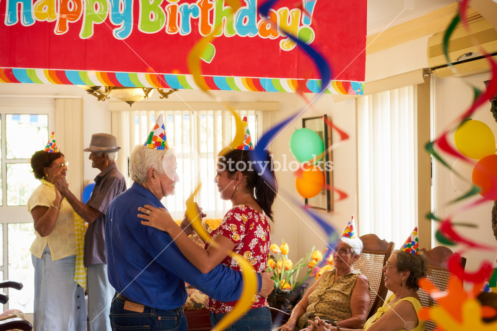 Group of old friends and family celebrating senior man birthday in retirement home. Happy elderly people having fun during party in hospice.