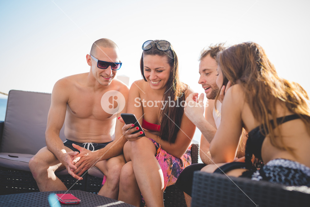 group of young multiethnic friends women and men at the beach bar in summertime using smartphone - happy hour, relax concept