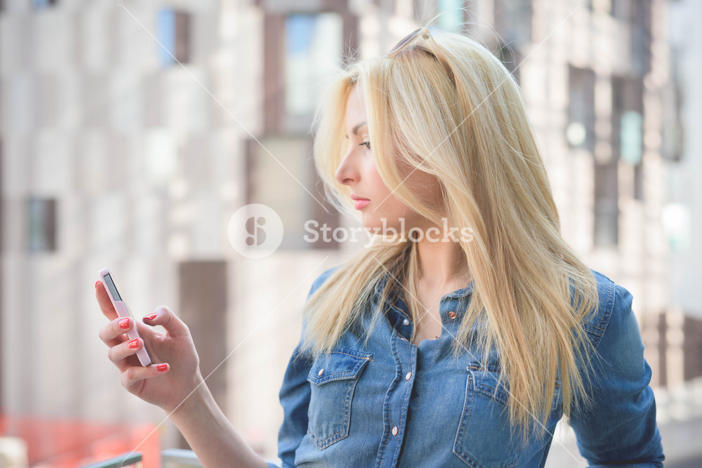 Half lenght of a young beautiful blonde caucasian girl leaning on a windowsill using a smartphone connected online looking down the screen - communication, technology, social network concept