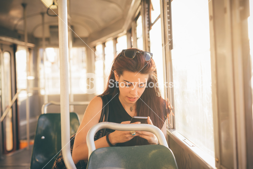 Half length of a young beautiful reddish brown hair caucasian woman using a smartphone on a tram - technology, social network, communication concept - looking down the screen