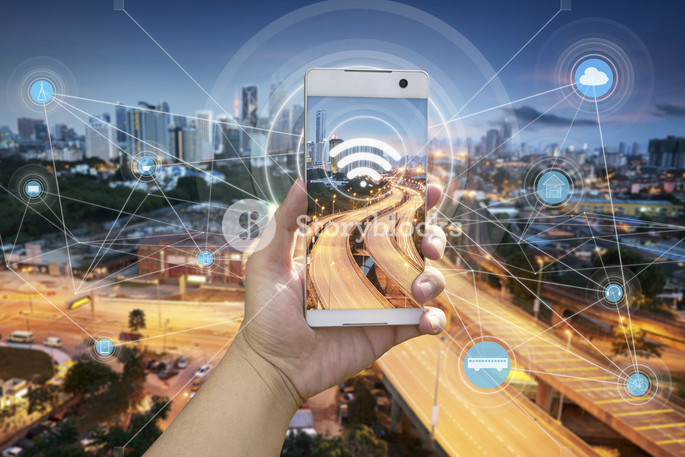 Hand holding white phone with city scape and wifi network connection concept
