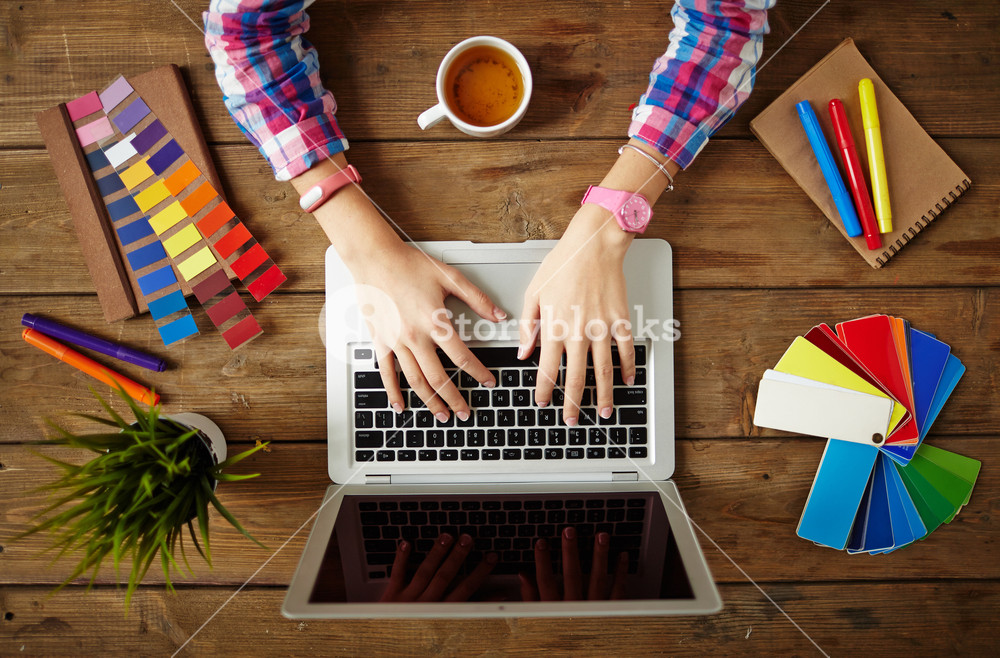 Hands of female designer working on laptop at the wooden table