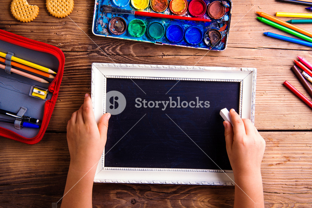 Hands of unrecognizable child writing with chalk on empty black board in white picture frame. Studio shot on wooden background. Flat lay, copy space.